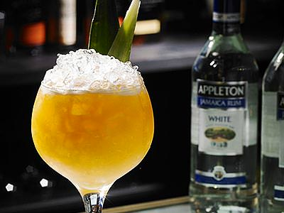 A large wine glass filled with an orange cocktail, crushed ice and pineapple leaves with a bottle of rum in the background