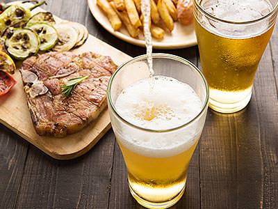 Two glasses of beer, a steak meal with vegetables and a plate of chips in the background