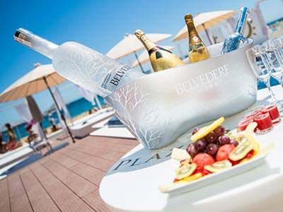 Some Belvedere vodka chilling in an ice bucket with fruit in the foreground and beds in the background