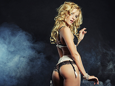 A stripper wearing underwear, with smoke in the background