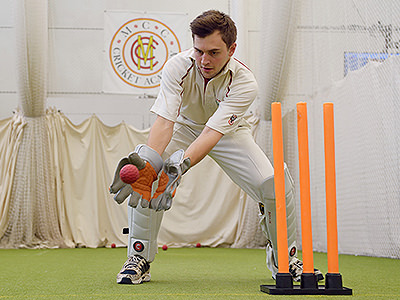 A man catching a cricket ball in front of orange wickets