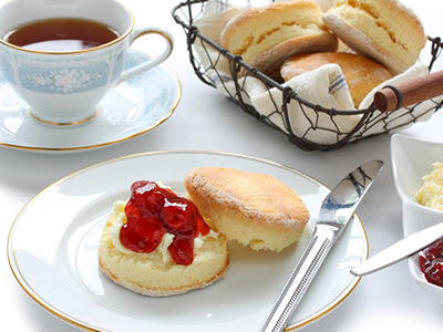 Close up image of a cup of tea, a scone with jam and cream and a basket of scones on a table