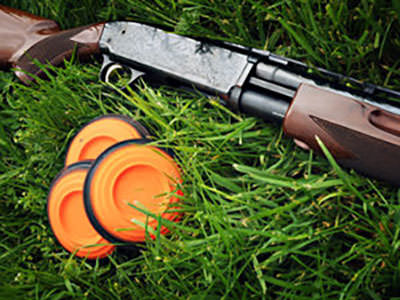 Close up of clay discs and shotgun in the grass