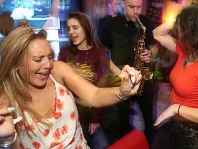 Girls dancing to man playing saxophone