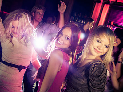 women dancing in an atmospheric club, with a barman in background