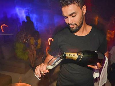 A waiter pouting a bottle of Moet into a champagne flute