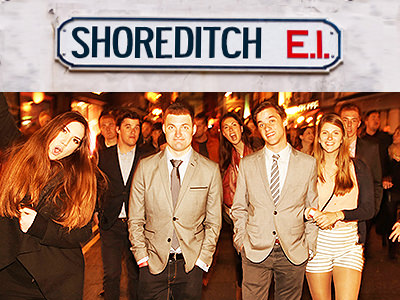 Smartly dressed men and women in the street with the Shoreditch street sign underneath them