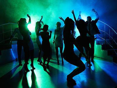 A group of people silhouetted whilst dancing, to a backdrop of green and blue lights