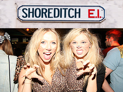 Two girls dressed as leopards and growling at the camera, with the Shoreditch street sign under them