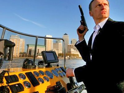 A man in a black suit, holding a handgun whilst driving a boat