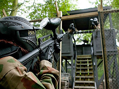 A view over the shoulder of a person aiming a paintball marker at a guard tower containing other players