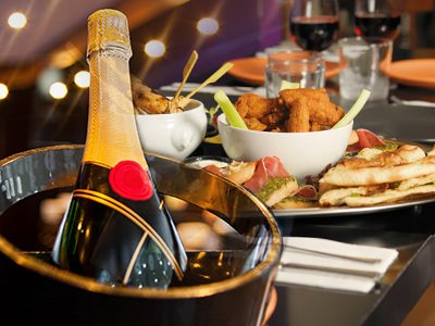 A plate of food overlaid with a bottle of champagne in an ice bucket