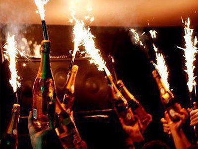 Champagne bottles being held in the air with sparklers attached