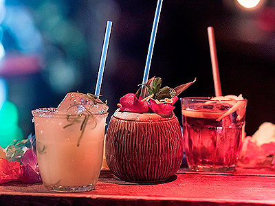 Three cocktails with straws in, one a wooden bench in Kanaloa bar