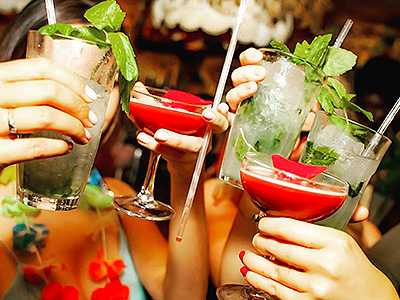 Girls' hands holding up their mojitos and bright red cocktails, one girl wearing a flower garland