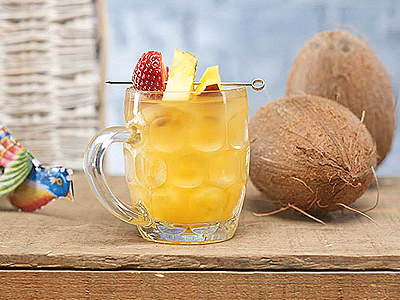 A yellow cocktail in a pint flagon on sand, next to a coconut