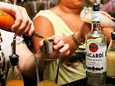 Two bar staff making cocktails at the bar, using Bacardi spirit