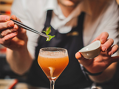 A woman holding tweezer and a sprig of basil over an orange cocktail