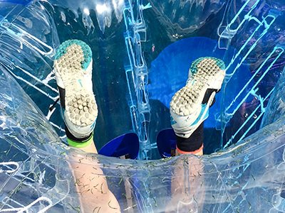 Close up of feet peeping out of the bottom of an inflatable zorb