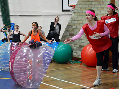 Three women running around in inflated zorbs on an outdoor pitch