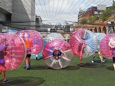 Five people in inflatable zorbs, standing on an outdoor pitch