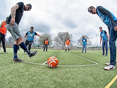 A group of people playing goggle football with an orange football