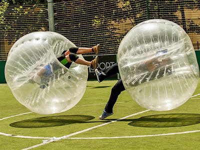 Two men in bubble football bubbles bouncing off each other
