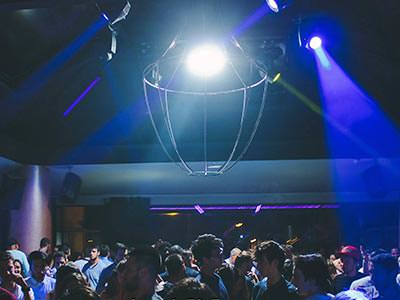 People dancing in a club to a backdrop of blue light