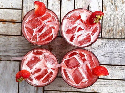 A top-down view of four red cocktails with strawberry garnishes