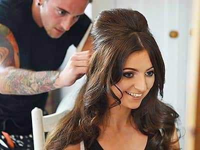 A woman having her hair touched up by a male stylist