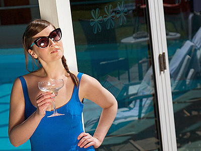 A woman in a blue vest and sunglasses, holding a martini glass