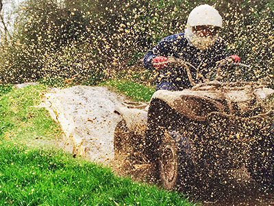 A man driving a mud buggy with mud flying in the air