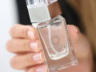 Close up of a woman's hand holding up a clear perfume bottle