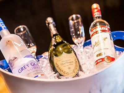 An ice bucket containing bottles of vodka, a bottle of champagne and two champagne glasses