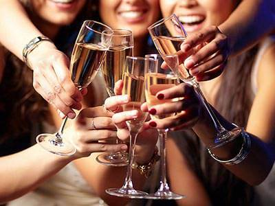 A group of women clinking glasses of champagne together