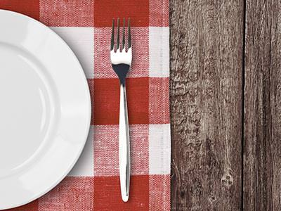 A white plate and fork on a red, checked tablecloth, set on a wooden table