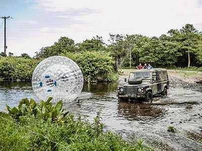 An inflated zorb and a 4x4 in a muddy stream