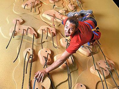 A man climbing on a climbing wall