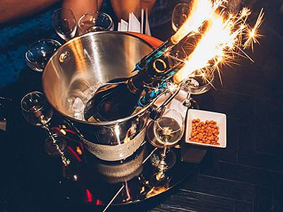 A bottle of champagne with a sparkler, in a silver ice bucket
