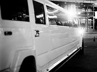 Black and white image of a white hummer limo, parked up