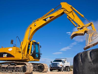A large yellow excavator with a tyre in the foreground and a white truck in the background