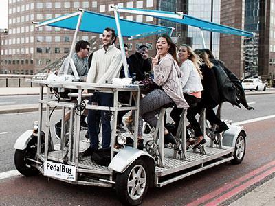 Group sat on a Pedi bus riding over London Bridge