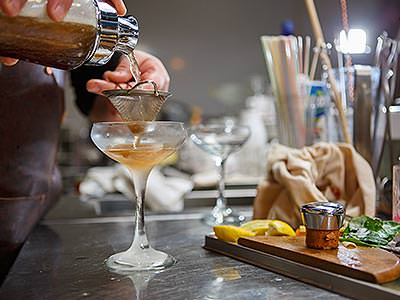 Close up of a bartender pouring a cocktail through a sieve and into a martini glass, with utensils next to him