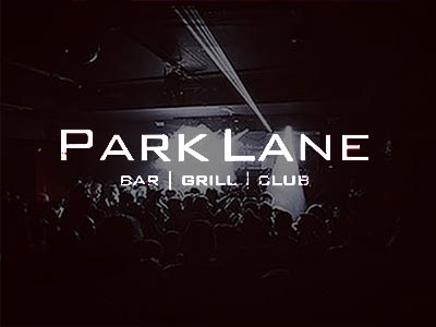 Dark image of people in a club, to a backdrop of white light