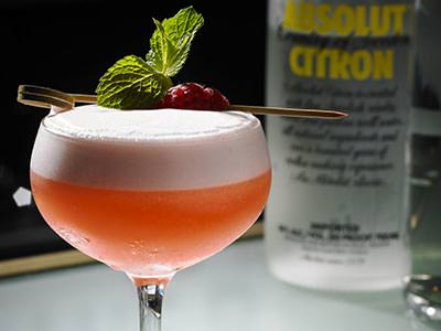 An orange, foamy cocktail garnished with a raspberry and mint sprig with a bottle of vodka in the background