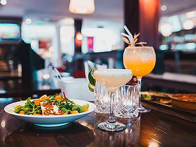 A plate of food on a table next to cocktails and empty rocks glasses