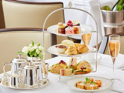 An afternoon tea with a glass of prosecco next to it