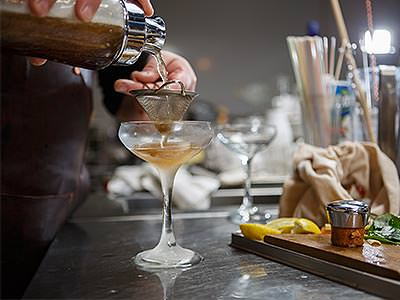 An amber cocktail being double strained into a chilled coupe glass
