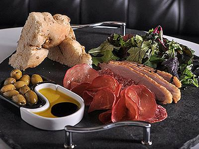 A platter of olives, bread, meats and salad