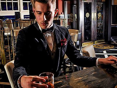 A man in a suit, holding a glass of whiskey on a table